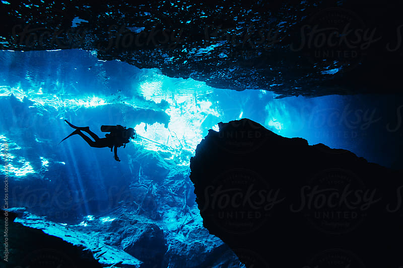 Silhouette of scuba diver exploring an underwater cave in a cenote in Yucatán Peninsula, Mexico by Alejandro Moreno de Carlos for Stocksy United