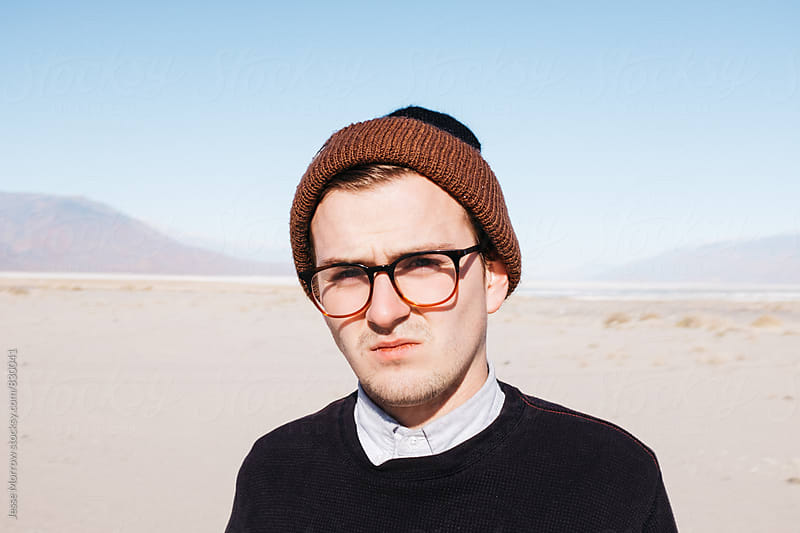 portrait of young male squinting in sunlight in desert sand by Jesse Morrow for Stocksy United