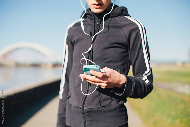 Woman in sportswear using mobile phone outdoors by Marija Mandic for Stocksy United