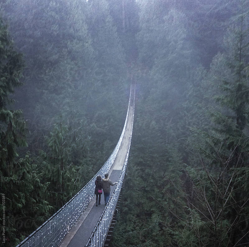 A couple walking on a suspension bridge by Luca Pierro for Stocksy United