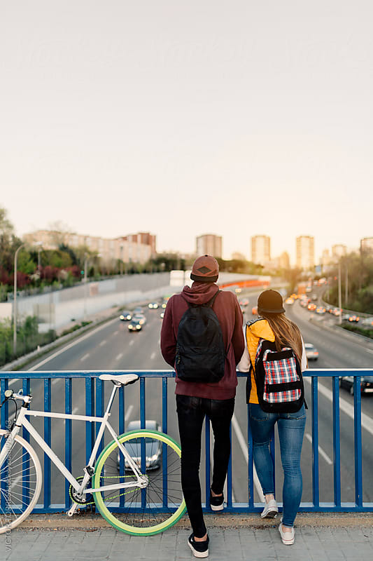 Happy Teen Couple Having a Walk Through a Bridge by Victor Torres for Stocksy United