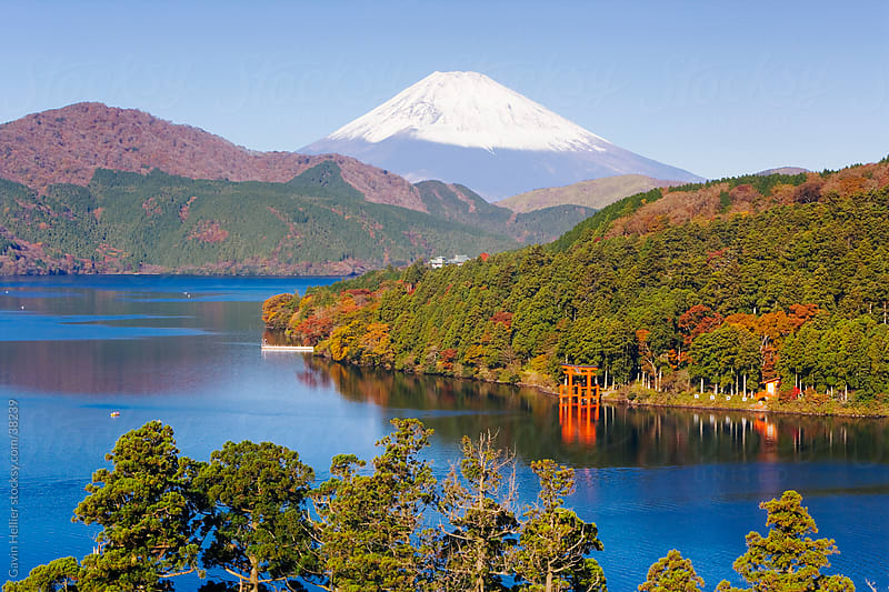 Japan, Central Honshu (Chubu), Fuji-Hakone-Izu National Park, Hakone, Mount Fuji (3776m) snow capped and viewed across lake Ashino-ko with the red  torii gates of Hakone-jinja rising from the lake by Gavin Hellier for Stocksy United