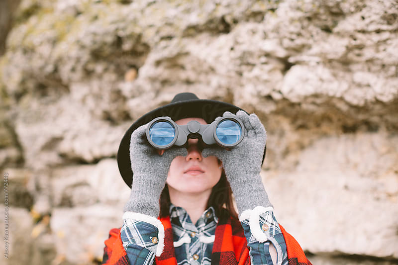 Woman looking with binoculars. by Alexey Kuzma for Stocksy United