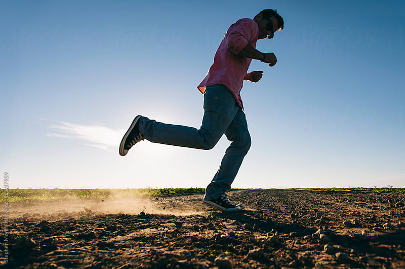 Man Dancing on Dirt Road by Stephen Morris for Stocksy United