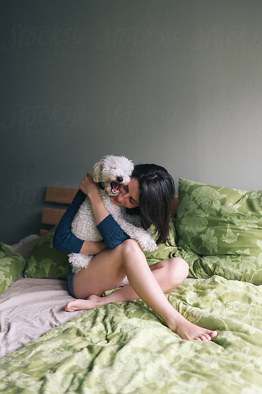 Brunette woman hugging with her white poodle on the bed  by VeaVea for Stocksy United