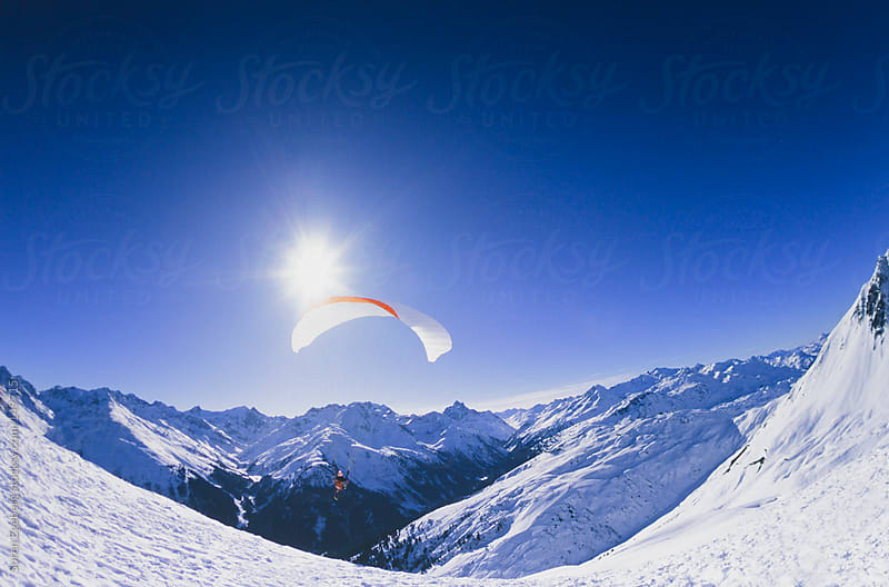 Man paragliding in winter mountain landscape with blue sky by Soren Egeberg for Stocksy United