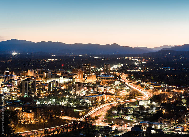 Asheville city at night with traffic motion by Matthew Spaulding for Stocksy United