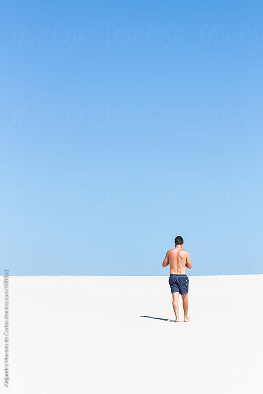 Back view of young man on the beach with blue sky and copyspace by Alejandro Moreno de Carlos for Stocksy United