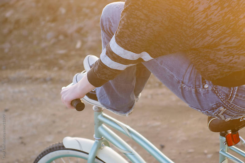 Young teen girl with her feet up on handle bars of bike.  by Tana Teel for Stocksy United