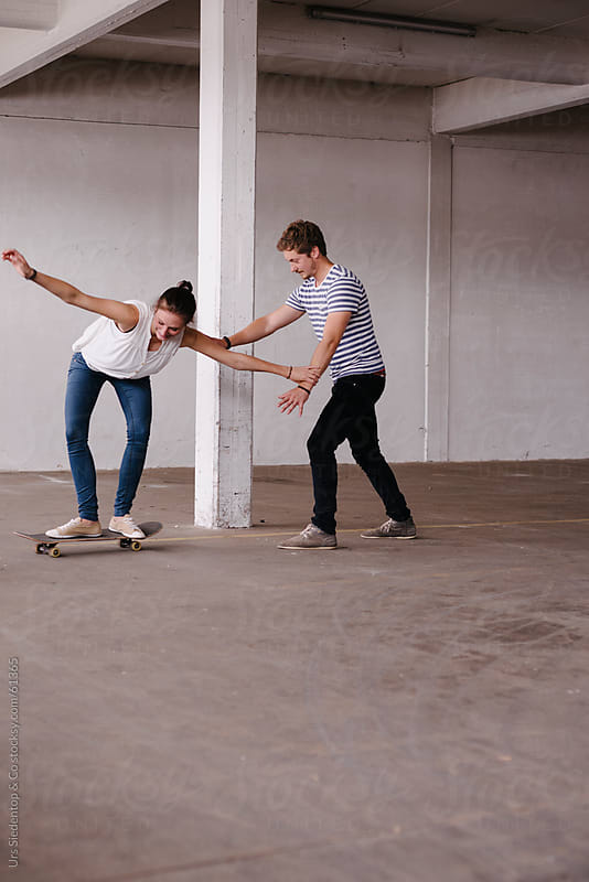 Young woman on skateboard - boyfriend gives support by Urs Siedentop & Co for Stocksy United