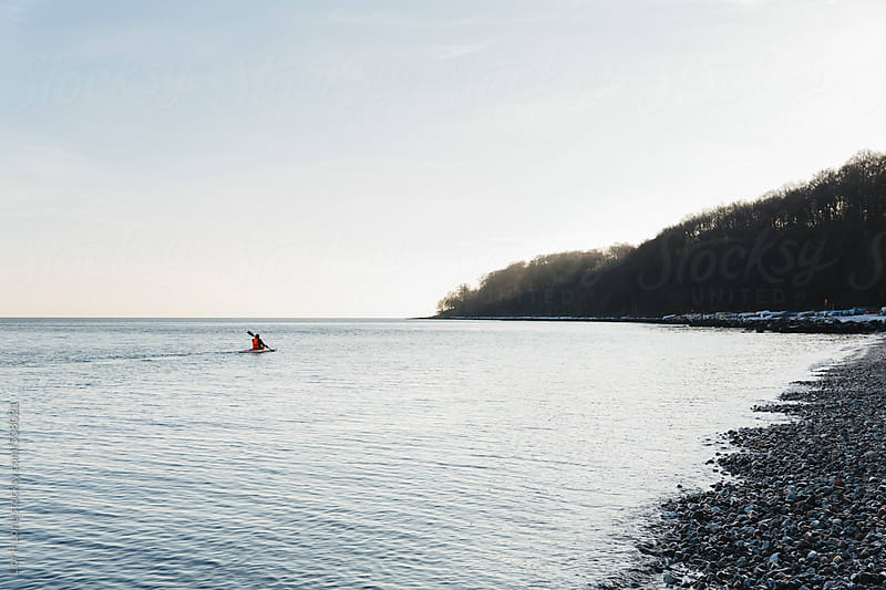 Man kayaking along the coast in winter by Lior + Lone for Stocksy United