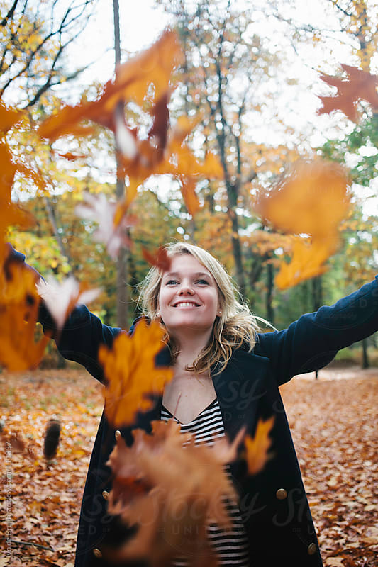 A young adult woman throwing a bunch of autumn leaves by Ivo de Bruijn for Stocksy United