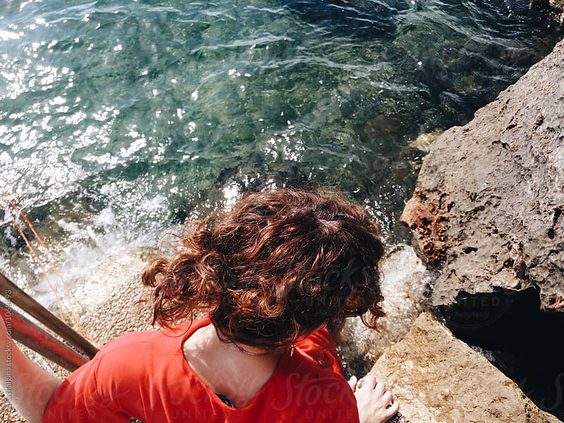 Back portrait of a young woman in front of sea by Anna Malgina for Stocksy United