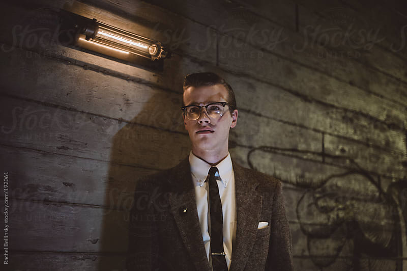 A dapper young man stands against a wall in a room with ambient light by Rachel Bellinsky for Stocksy United