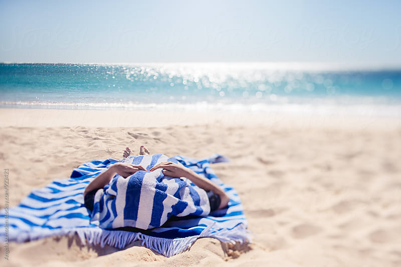 Child lying on a blue and white striped towel at the beach on a hot summer day by Angela Lumsden for Stocksy United