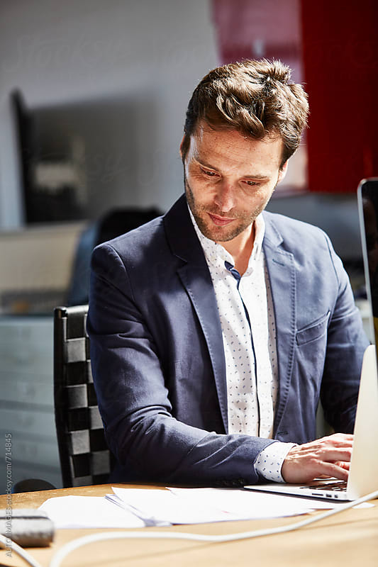 Businessman Looking At Document While Using Laptop by ALTO IMAGES for Stocksy United