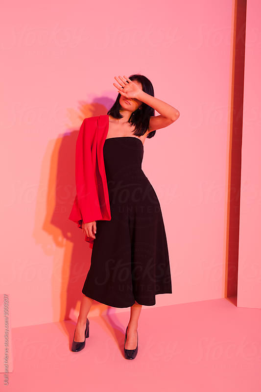 fashion model wearing black outfit and red jacket posing under colored lights by Ulaş and Merve for Stocksy United