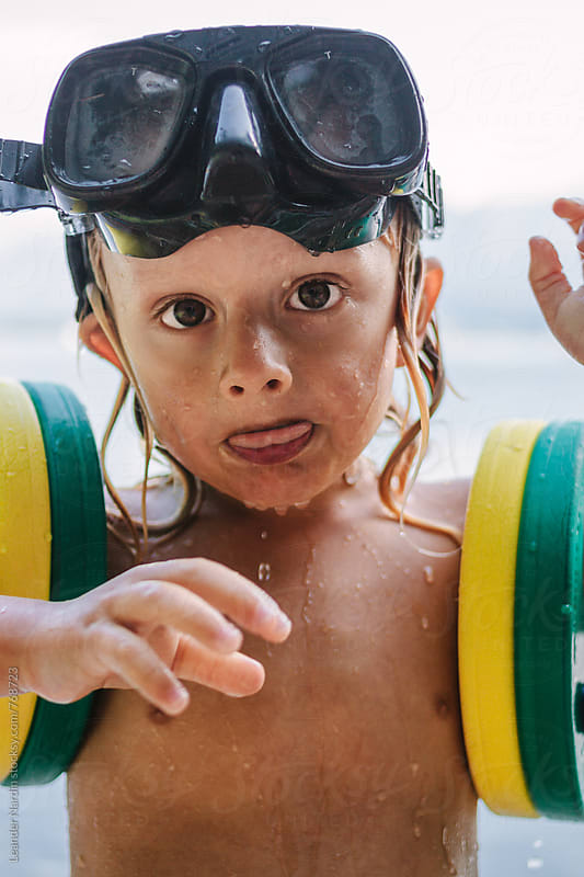 wet toddler with diving goggles on the head and swimming rings by Leander Nardin for Stocksy United