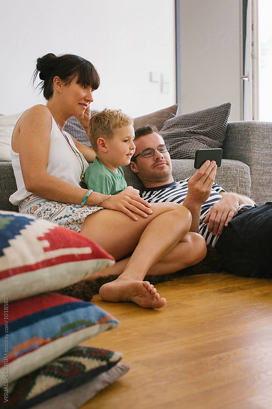 Family at Home - Young Parents With Small Boy Watching Video on Smartphone by Julien L. Balmer for Stocksy United