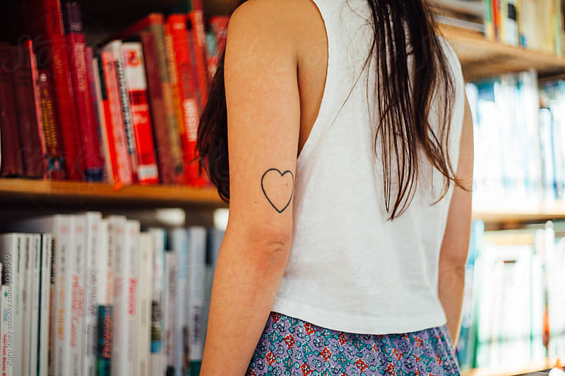 Woman with heart tattoo looking at bookshelf by Kara Riley for Stocksy United