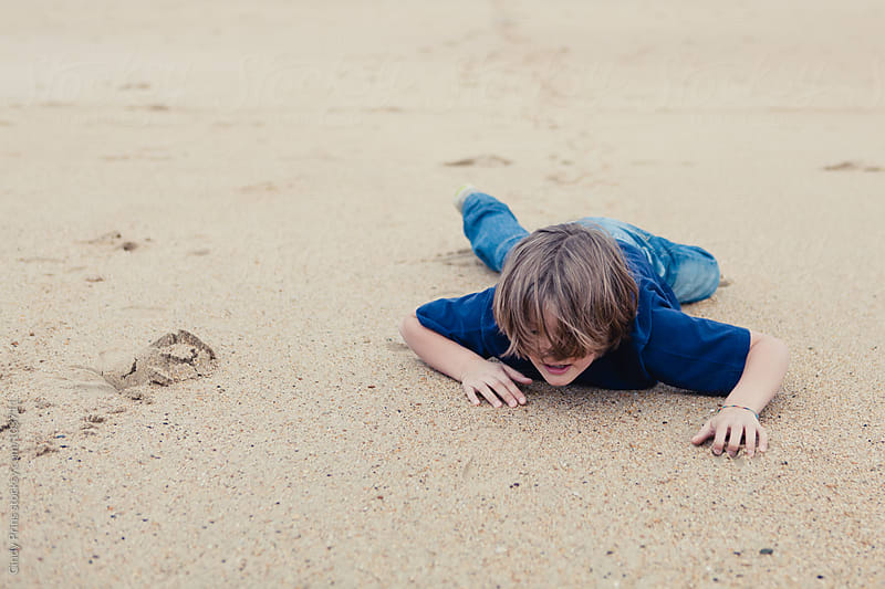 Boy lying on the sand of the beach crawling forward by Cindy Prins for Stocksy United
