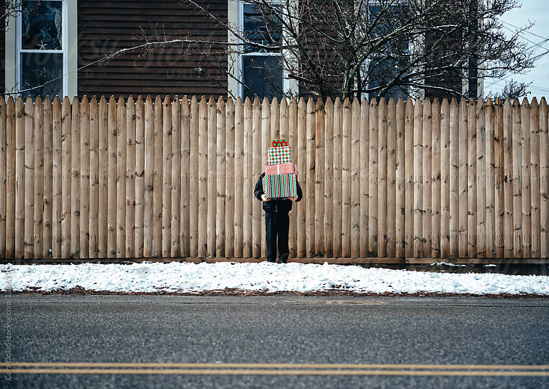 Child standing on snowy sidewalk holds stack of Christmas presents taller than his head by Cara Dolan for Stocksy United