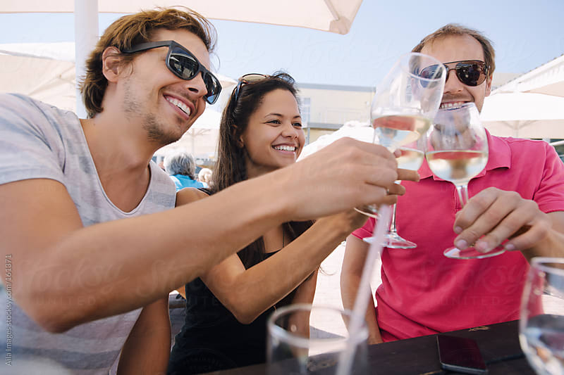 Three Friends enjoying Wine on Summers Day by Aila Images for Stocksy United