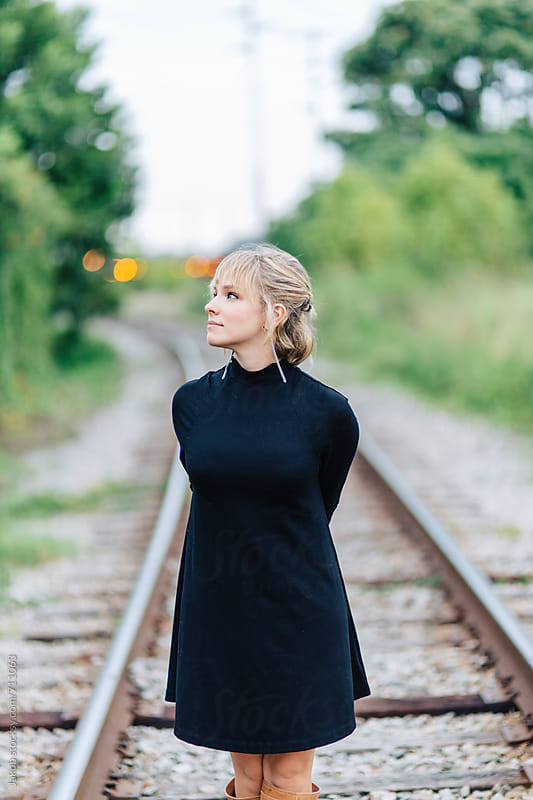 Beautiful young woman standing by train tracks by Jakob for Stocksy United