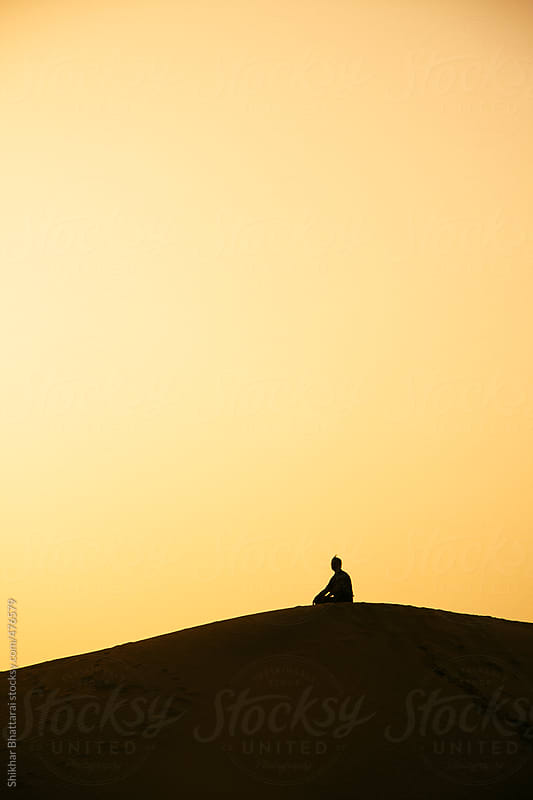 A silhouetted man sitting on top of a sand dune, contemplating. by Shikhar Bhattarai for Stocksy United