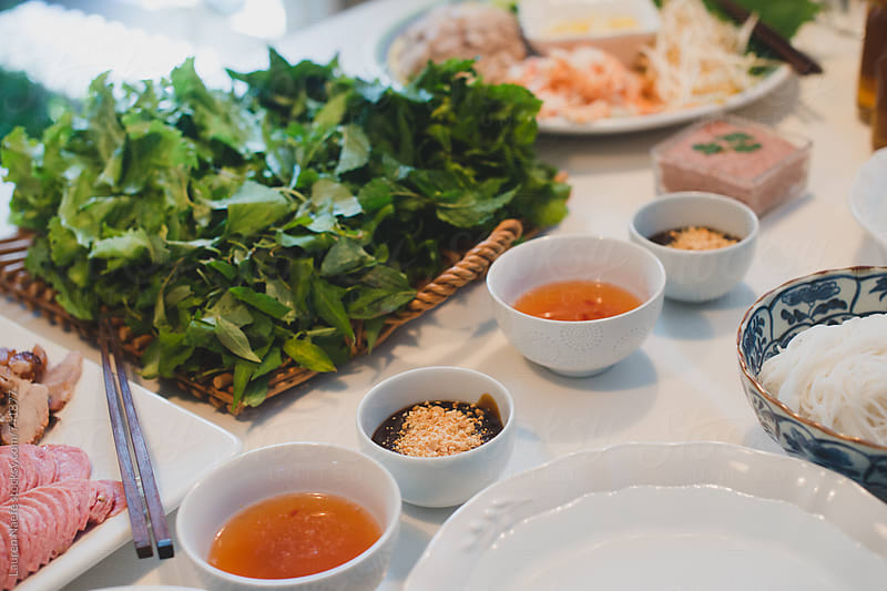 Fish sauce, peanut sauce and lettuce on table by Lauren Naefe for Stocksy United