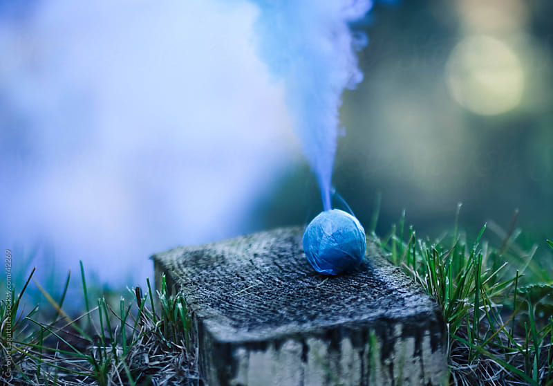 A round smoke bomb, with beautiful, blue smoke pouring out the top. by Carolyn Lagattuta for Stocksy United