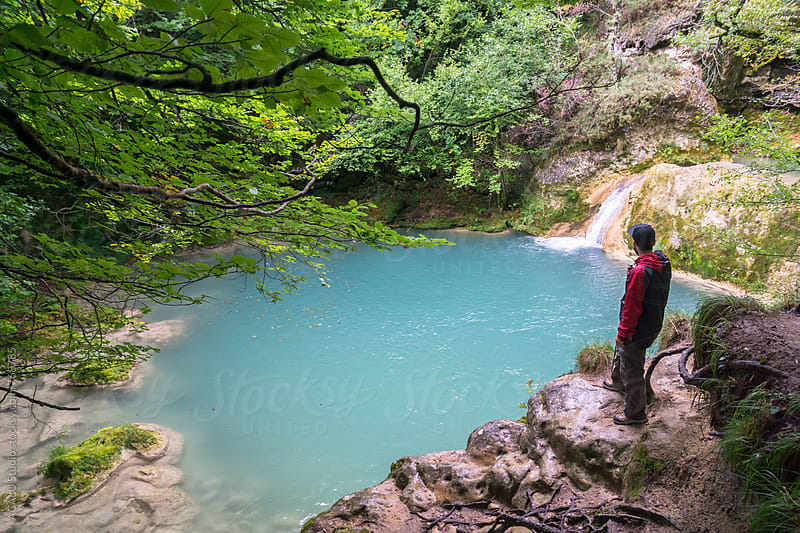 Man looking an amazing turquoise river by ACALU Studio for Stocksy United