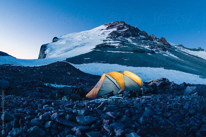 Tent camping next to a mountain glacier by Chris Werner for Stocksy United