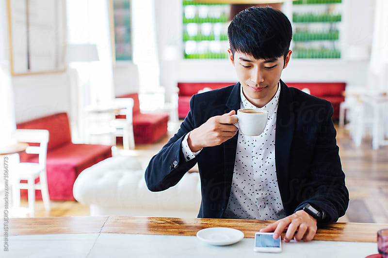 Young businessman using phone whilst having breakfast in a coffee bar.  by BONNINSTUDIO for Stocksy United