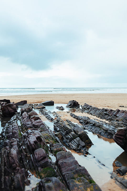 Rocks and rock pools on a sandy beach by Suzi Marshall for Stocksy United