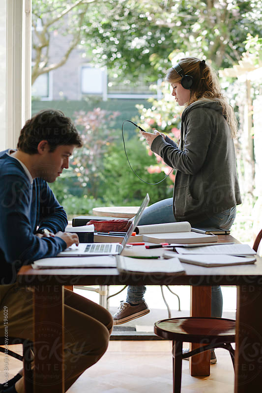 Two students studying at their parents home by Ivo de Bruijn for Stocksy United