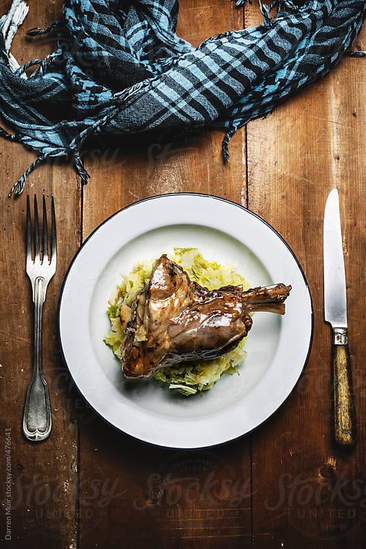 Braised lamb shank dinner.  by Darren Muir for Stocksy United