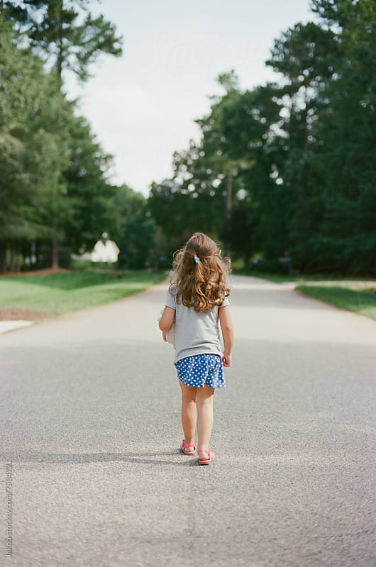 Young girl with long hair walking down the middle of a road by Jakob for Stocksy United