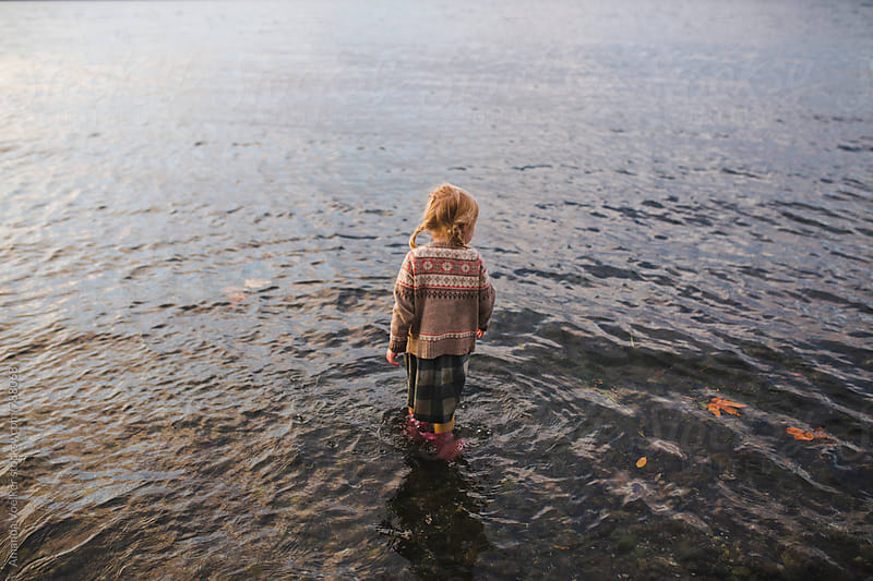 A little girl stands fully dressed in Cold Water at Sunset by Amanda Voelker for Stocksy United