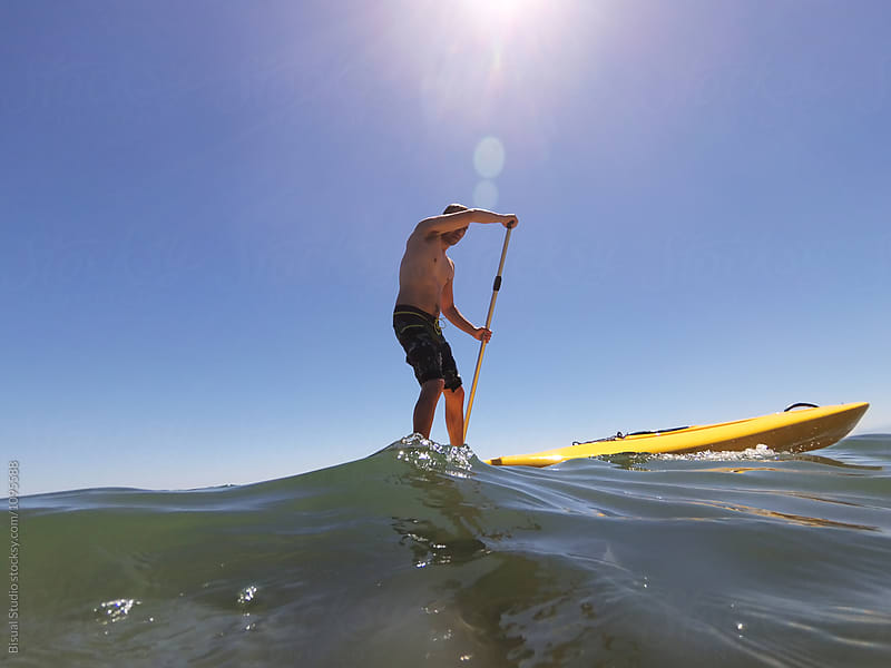 Man having fun and making paddle surf by Bisual Studio for Stocksy United