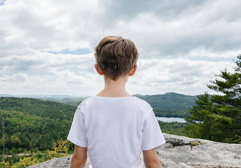 Boy stands at the top of the mountain, looking at the view by Cara Dolan for Stocksy United