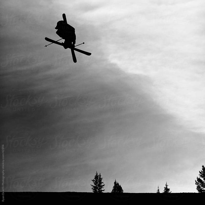 Black and White Silhouette of Skier in Mid-air by Ryan Dearth Photography for Stocksy United