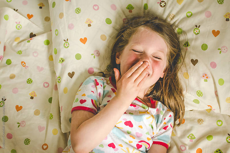 Lilttle girl in pajamas giggling in her bed by Lindsay Crandall for Stocksy United