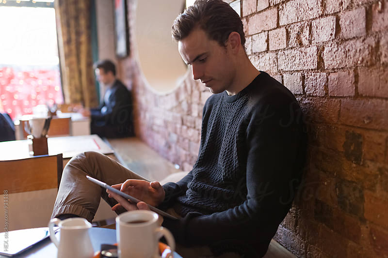 Young Man Using Digital Tablet in a Coffee Shop by HEX. for Stocksy United