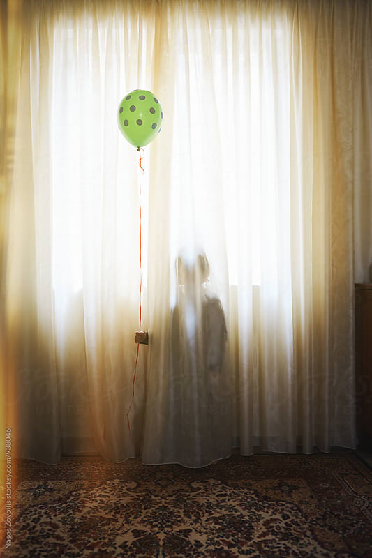 5 years old boy hiding behind a curtain by Nasos Zovoilis for Stocksy United