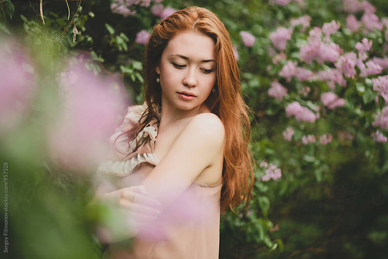 Portrait of beautiful young woman in blossom garden by Sergey Filimonov for Stocksy United