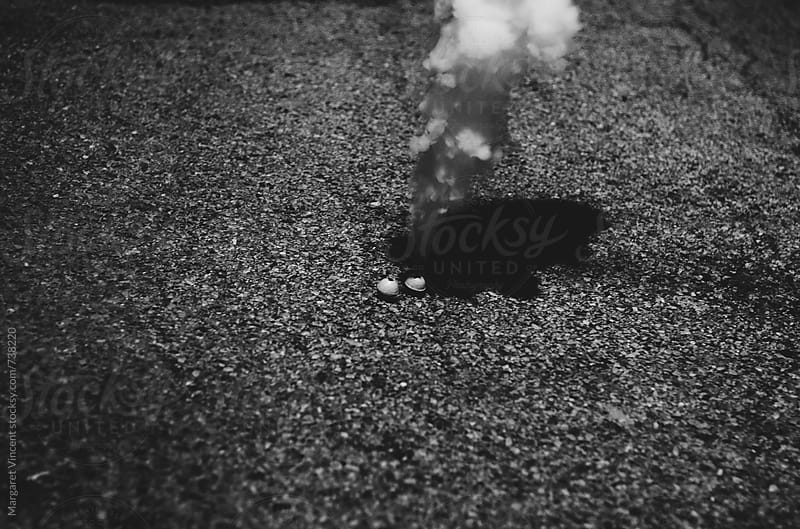 two smoke bombs in an alley by Margaret Vincent for Stocksy United