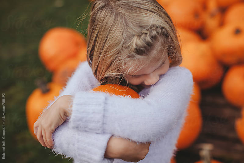 Cute little girl holding pumpkin by Rob and Julia Campbell for Stocksy United