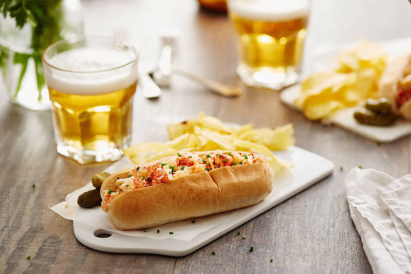 Lobster roll on plastic board with pickles by Martí Sans for Stocksy United