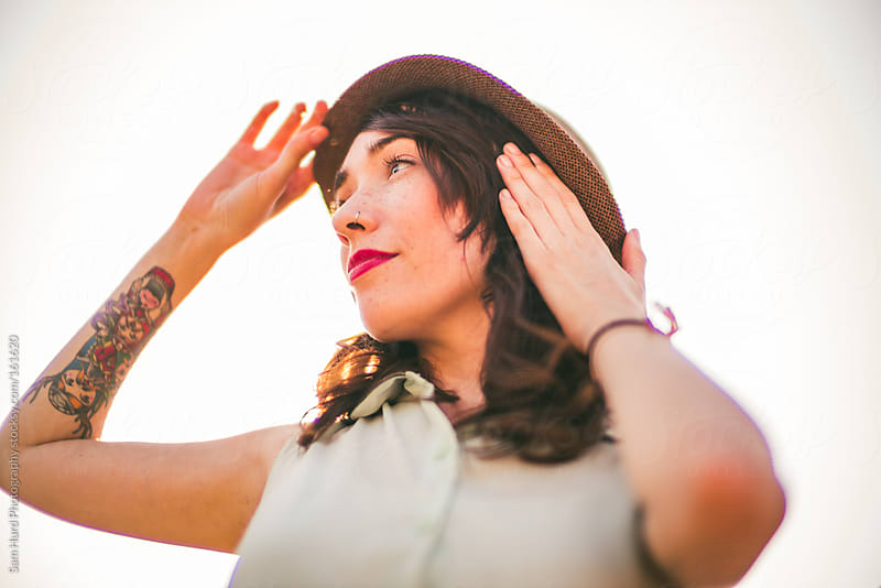 woman fixing hat by Sam Hurd Photography for Stocksy United
